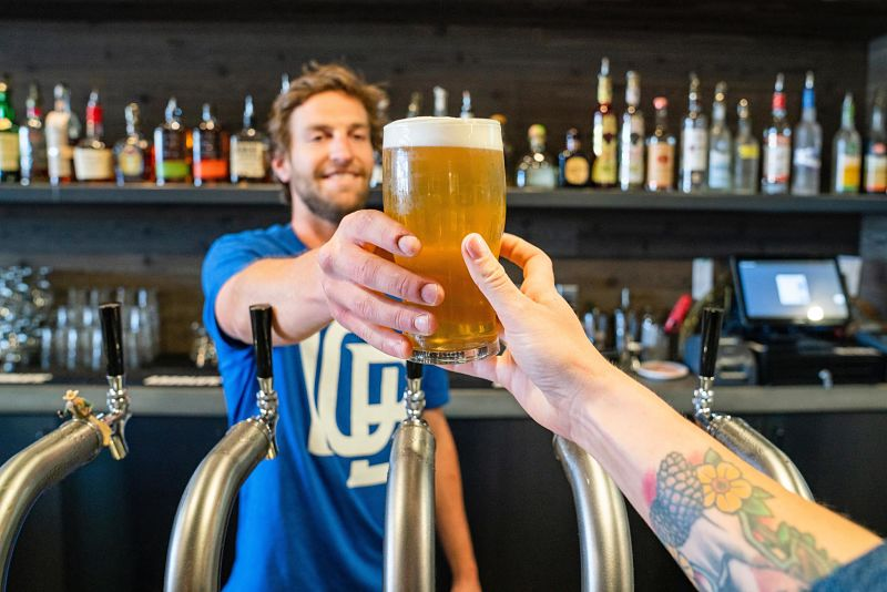 Homem entregando uma cerveja
