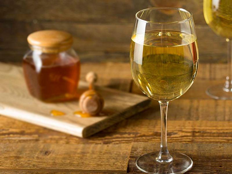Taça de hidromel acompánhado com pote de mel ao fundo